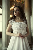 Young victorian lady in white dress. Portrait of a beautiful young victorian lady in white dress.Russian palace royalty free stock images