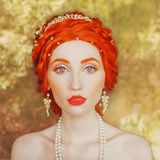 Young victorian redhead princess with freckles in castle. Fabulous portrait of rococo queen against backdrop of stone wall. Renaissance duchess. Victorian royalty free stock images