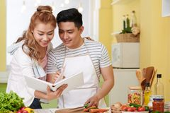 Searching for recipe. Young Vietnamese couple searching for good recipe in a cookbook Stock Photos
