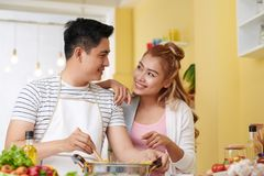 Cooking spaghetti. Young Vietnamese men cooking spaghetti for his girlfriend royalty free stock photo