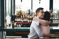 Hugging friend. Young Vietnamese men is happy to meet his friend in bar Royalty Free Stock Images