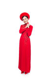 Young vietnamese woman in Ao Dai Dress with praying gesture wish. Ing you good luck Royalty Free Stock Image