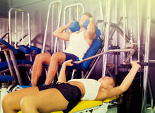Young vigorous woman lying on back on bench and lifting weights Royalty Free Stock Photos