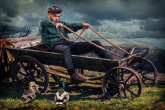 Young villager in the old cart. Young villager in the old horse cart without horses having a ride. Modern man using vintage tool. Country side background Royalty Free Stock Photo