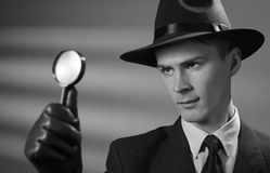 Young vintage detective holding a magnifying glass. Handsome young vintage detective wearing a hat holding a magnifying glass in his gloved hand as he searches Royalty Free Stock Image