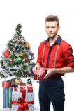 Young vintage man holding gift near christmas tree Royalty Free Stock Photos