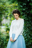 Young vintage style woman posing in a vineyard. Portrait of a young slim beautiful girl with retro hair wearing a white blouse, blue skirt, posing against a Royalty Free Stock Images