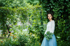 Young vintage style woman posing in a vineyard. Portrait of a young slim beautiful girl with retro hair wearing a white blouse, blue skirt, posing against a Stock Photos