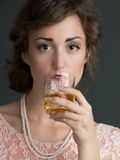 Young vintage woman holding a drink in front of her Royalty Free Stock Image