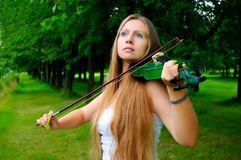 Young violinist. Young girl playing the green violin stock image