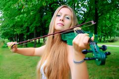Young violinist. Young girl playing the green violin stock photo