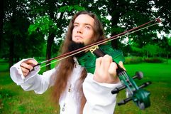 Young violinist. Young man playing the green violin stock photography