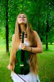 Young violinist. Young girl holding the green violin royalty free stock photos