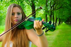 Young violinist. Young girl playing the green violin stock photos
