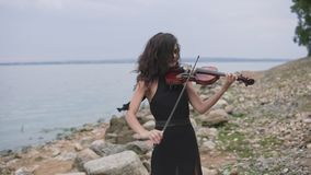 Young violinist in black dress plays near sea. Beautiful girl with violin stock video