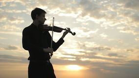 A young violinist in a black shirt, playing on the roof. stock video footage