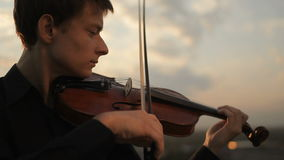 Young violinist playing at sunset. Close-up of strings and bow stock footage
