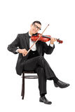 Young violinist playing a violin seated on a chair Royalty Free Stock Photos