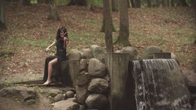 Young violinist plays with inspiration. Girl in dress playing violin in forest. Elegant girl in black dress playing violin in forest with waterfall. Beautiful stock video footage