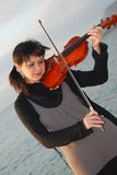 Young violinist at sea Stock Images