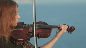 Young violinist in tracery dress plays on a rock stock video footage