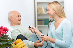 Young visiting relative measures blood pressure of royalty free stock images