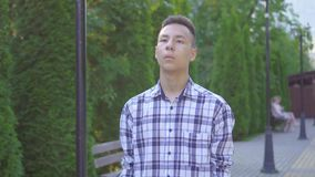 Young visually impaired asian man with a cane is in the park close up stock video