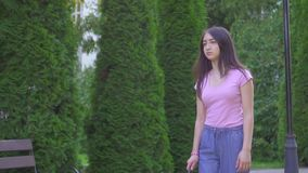 Young visually impaired asian woman with a cane is in the park slow mo stock video