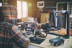 Free Young Vlogger Man Editing Video On Laptop And Checking Smartphone Royalty Free Stock Photo - 124958995