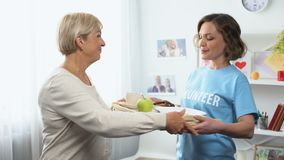 Young volunteer bringing breakfast tray for aged lady, social support assistance. Stock footage stock video footage
