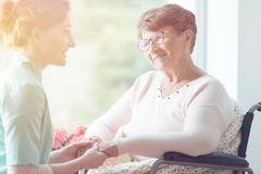 Young volunteer and elderly woman. Young volunteer holding hands of smiling elderly women in a wheelchair Royalty Free Stock Image