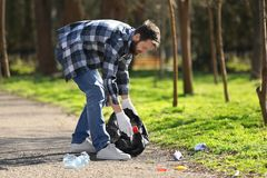 Young volunteer picking up litter. In park Stock Image