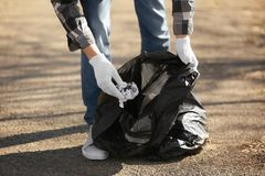 Young volunteer picking up litter in park. Closeup Royalty Free Stock Photo