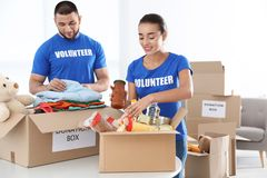 Young volunteers collecting donations. At table indoors royalty free stock photos