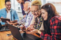 Young volunteers help senior people on the computer Royalty Free Stock Image