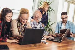 Young volunteers help senior people on the computer. Young people giving senior people introduction to internet stock image