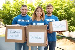 Young volunteers holding boxes with donations. For poor people outdoors royalty free stock image