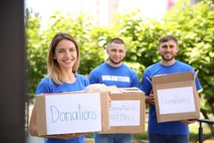 Young volunteers holding boxes with donations. For poor people outdoors stock images