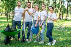 young volunteers posing in park with watering can shovel rake and wheelbarrow stock image