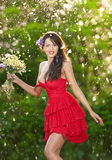 Young voluptuous brunette holding a wild flowers bouquet in a sunny day. Portrait of beautiful woman with low-cut red dress smiling, outdoor shot. Provocative Stock Image