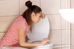 Young vomiting woman near toilet bowl at. Home Stock Photo