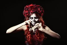 Young voodoo witch with muertos makeup (sugar skull) piercing doll Stock Images