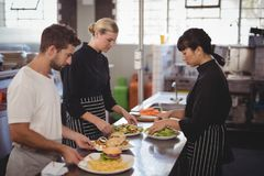 Young wait staff with fresh food in plates on kitchen counter Royalty Free Stock Photos