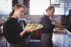 Young wait staff holding fresh salad plates while standing in commercial kitchen Royalty Free Stock Photos