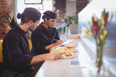 Young wait staff sitting with clipboard and food at counter. In coffee shop Royalty Free Stock Image