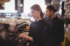Young wait staff using espresso maker at coffee shop. Young wait staff using espresso maker standing in coffee shop Royalty Free Stock Photography