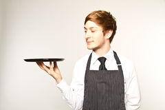 Young waiter. Standing in white studio Stock Photo