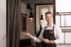 Young waiter in apron with tablet computer. At workplace Stock Photos