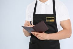 Young waiter in apron taking order. On light background Royalty Free Stock Image
