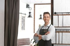 Young waiter in apron. At workplace Stock Photo